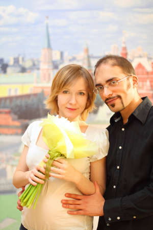 man in glasses embracing beauty blond girl with flowers bouquet, looking at camera photo
