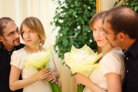 man in glasses and beauty blond girl with flowers bouquet standing near mirror photo