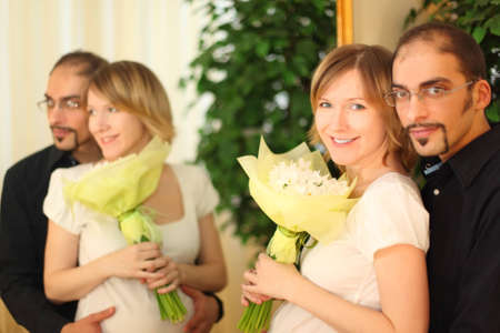 man in glasses and beauty blond girl with flowers bouquet standing near mirror and smiling photo