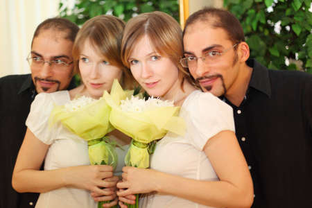 man in glasses and beauty blond girl with flowers bouquet standing near mirror and looking at camera photo