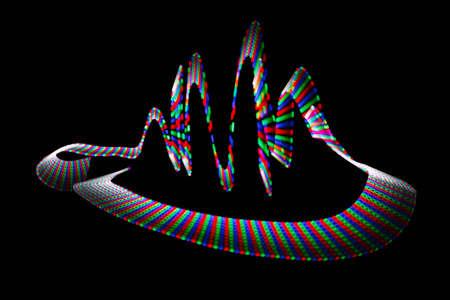 Multi-coloured wavy trace of light-emitting diode on black background. photo