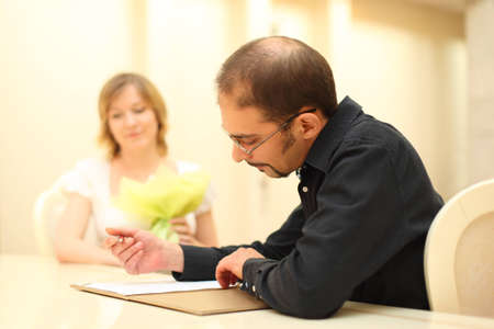 man in black shirt making sign on wedding documents, bride on background photo
