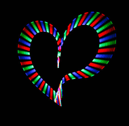 Multi-coloured shone heart on black background. Love symbol. photo