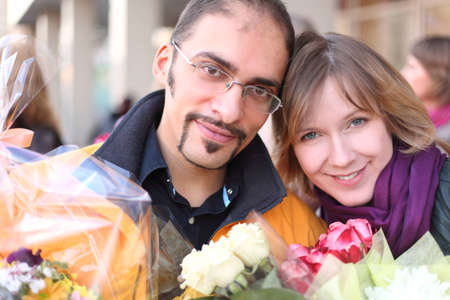 outdoor portrait of man in glasses and beauty blond girl with flower bouquets, looking at camera and smiling photo