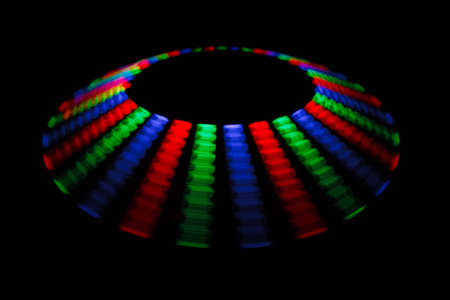 segment: Colorful trace rotating LED in form of a disc on a black background. Stock Photo