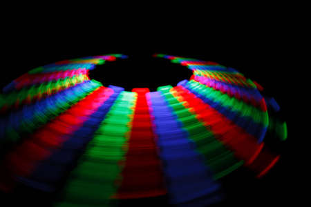 Colorful trace rotating LED in form of a disc on a black background.  photo