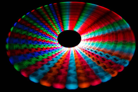Colorful glowing trail rotating LED, in form of a disc. Isolated on black background. photo