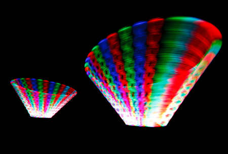 Colorful glowing trail rotating LED, in form of two cones on black background. photo