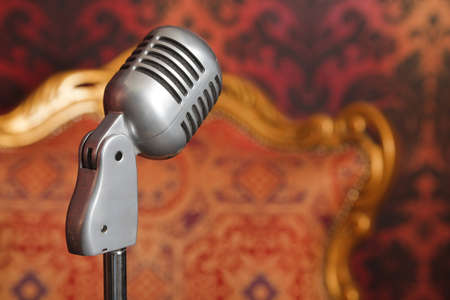 vintage metal microphone on a stand photographed against a background of yellow-red ornament wallpaper and armchair photo