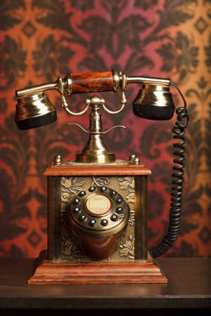 accents: old phone is made of metal on a wooden table. withdrawn against the arnament. focus on phone Stock Photo