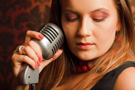 personas abrazadas: mujer se abraza a la vendimia micrófono de mano colocado sobre un soporte. cabeza girada hacia un lado. los ojos cerrados
