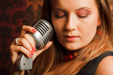 woman hugged hand vintage microphone placed on a stand. head turned to one side. eyes closed photo
