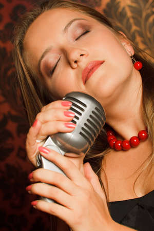 woman hugged her hands vintage microphone placed on a stand. eyes closed and head up photo