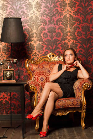 woman in black dress sitting on a vintage chair and looks up, holding a red beads. near the old phone on a wooden table and black lamp photo