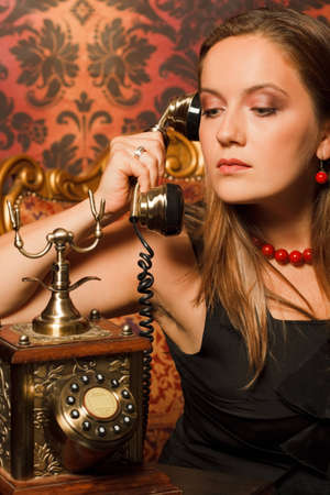 woman in black dress sitting on a vintage chair and talking on the old phone. holds the tube in his hands and looks down photo