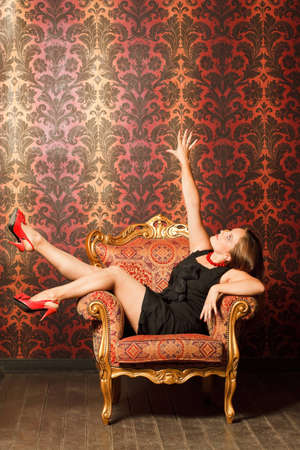mirth: Woman in red shoes and a black dress sitting on a chair with a red-yellow wallpaper. hand is raised up. joy