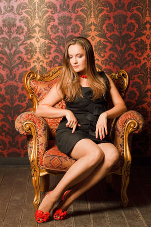 Woman in red shoes and a black dress sitting on a chair with a red-yellow wallpaper. long hair, looking down. think Stock Photo - 11574601