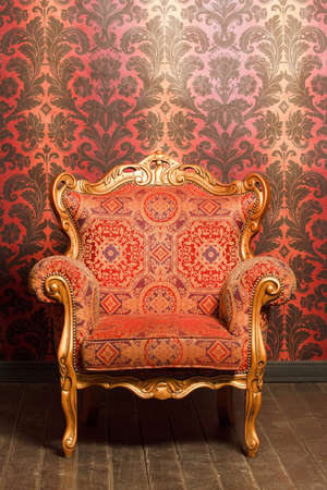 vintage red-yellow chair with gold accents standing beside the wall. wooden floor Stock Photo - 11574607