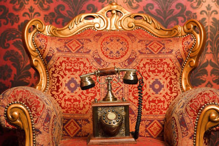 accents: old phone is a red chair with gold accents, red vintage wallpaper. Focus on phone