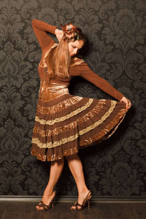 uneasiness: woman in a brown dress standing beside a wall. keeps the bottom of her skirt with his hand, looking at her skirt. black and gray pattern on the wallpaper wall.