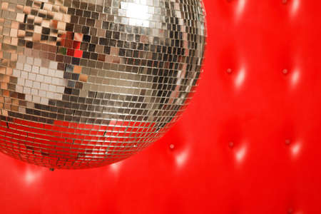 dance mirror ball on red leather background photo