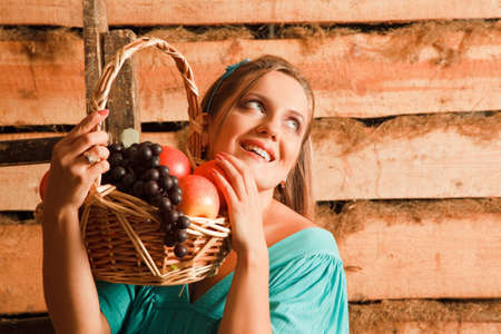 hand basket: woman in a turquoise dress holding a basket of apples and grapes in their hands. looks up. wooden wall. smiles