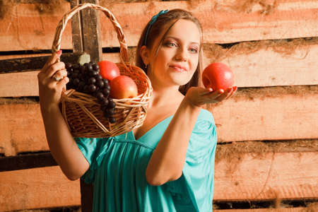 woman in a turquoise dress holding a basket of apples and grapes in their hands. holding an apple and looked at him. wooden wall photo
