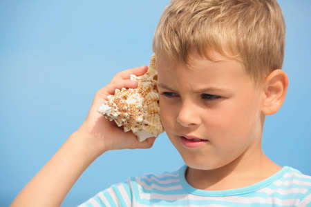 conch shell: little boy with shell listening noise of sea. focus on left eye. Stock Photo
