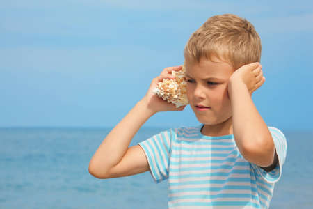 conch shell: little boy with shell listening noise of sea. sea in out of focus. Stock Photo