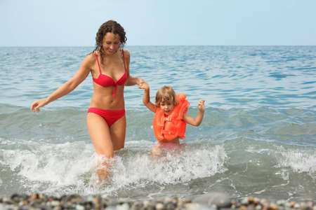 lifejacket: attractive woman with her daughter in water. little girl wearing lifejacket.