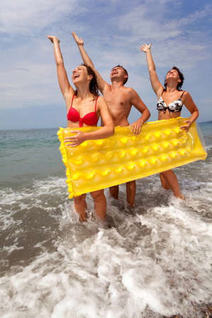trio of young people have fun on seacoast and hold yellow inflatable mattress. youth group has rest on beach. guy and two girls stand ashore having lifted hands. Stock Photo
