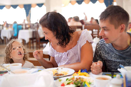 resort life: young caucasian family having dinner together. mother, father and daughter in cafe. mum feeds girl from plug Stock Photo
