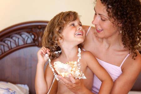ropa interior: Close-up retrato de la joven madre feliz con su hija jugando con cáscara de nuez en la cama en la habitación de hotel