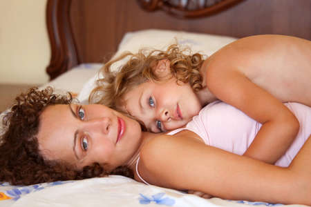 pyjamas: mother embracing cuddling daughter in bed.  Portrait of mum and her little girl lying on bed.