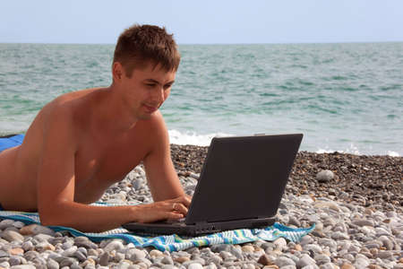 young man working on his notebook on seacoast. portrait of guy with laptop lying on beach.  photo