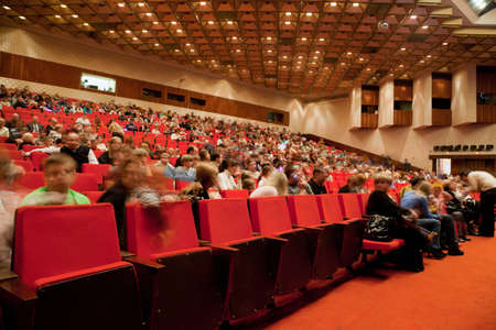 theater audience: Moscow - February 22: Adults and children sit on red chairs in auditorium of circus of dancing fountains AKVAMARIN before a show on February 22, 2010 in Moscow. Editorial