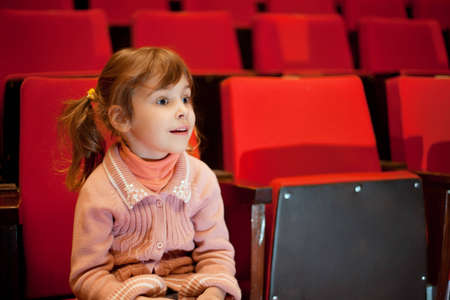 spectator: Smiling little girl sitting on armchairs at cinema