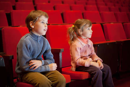 spectators: boy and  little girl sitting on armchairs at cinema, steadfastly looking