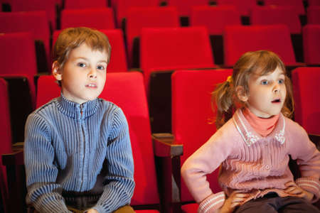 family movies: boy and  little girl sitting on armchairs at cinema, girl has opened mouth Stock Photo