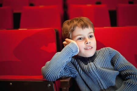 boy sitting on armchairs at cinema, steadfastly looking photo