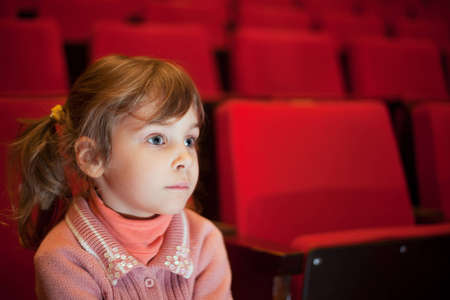 scared child: little girl sitting on armchairs at cinema, steadfastly looking Stock Photo