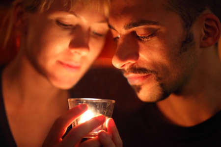 man and woman keeping glass candle and looking at it. focus on man's left eye.