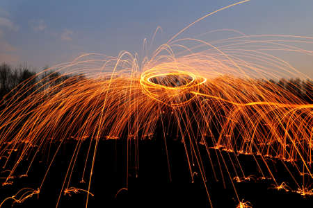 abstract background with orange sparklers flying away at night time outdoor photo