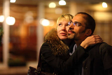 coldly: coldly nightly street. woman is emracing her man. focus on mans face. Stock Photo