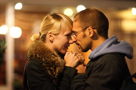 coldly: man and woman is cuddling in coldly nightly fall city. focus on womans face.