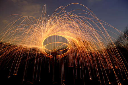 abstract background with orange sparklers flying away at night time outdoor, view from below photo