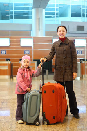 young mother and little girl with suitcases standing at airport photo