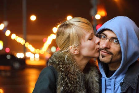 coldly: street of night coldly fall city. woman is kissing her man. focus on mans face.