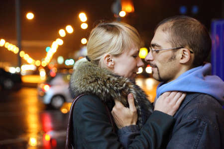 coldly: nightly street of coldly fall city. man and woman is embracing.