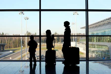 gente aeropuerto: silueta de la madre, hijo e hija con el equipaje de pie cerca de una ventana en el aeropuerto